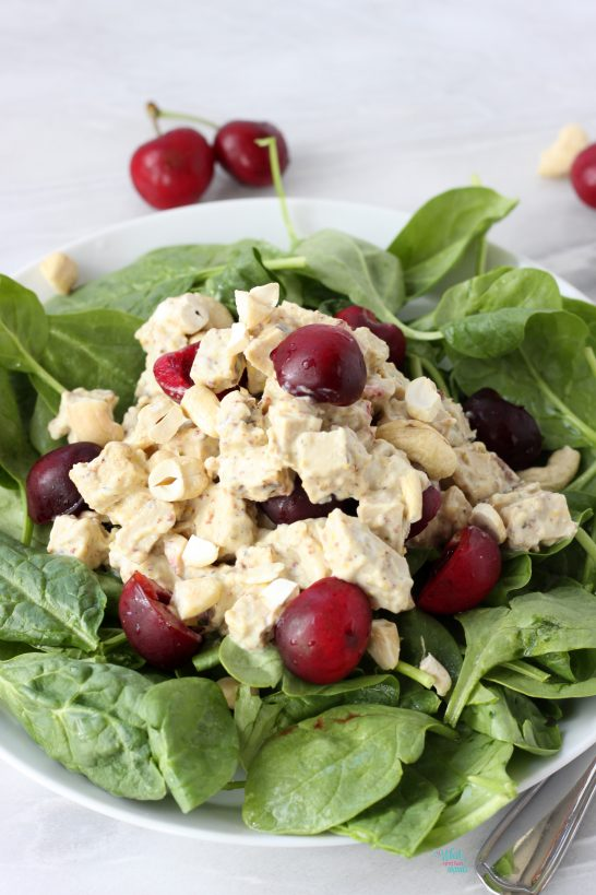 Vegan Cherry Cashew Chicken Salad on top of baby spinach