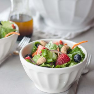 Simple and delicious salad packed with fresh sweet berries on a bed of romaine, carrots, and red onion dressed with a basic balsamic vinaigrette and topped with nuts. Great for lunch, dinner as a main or side, or your next get together for sharing. Naturally gluten free and vegan.