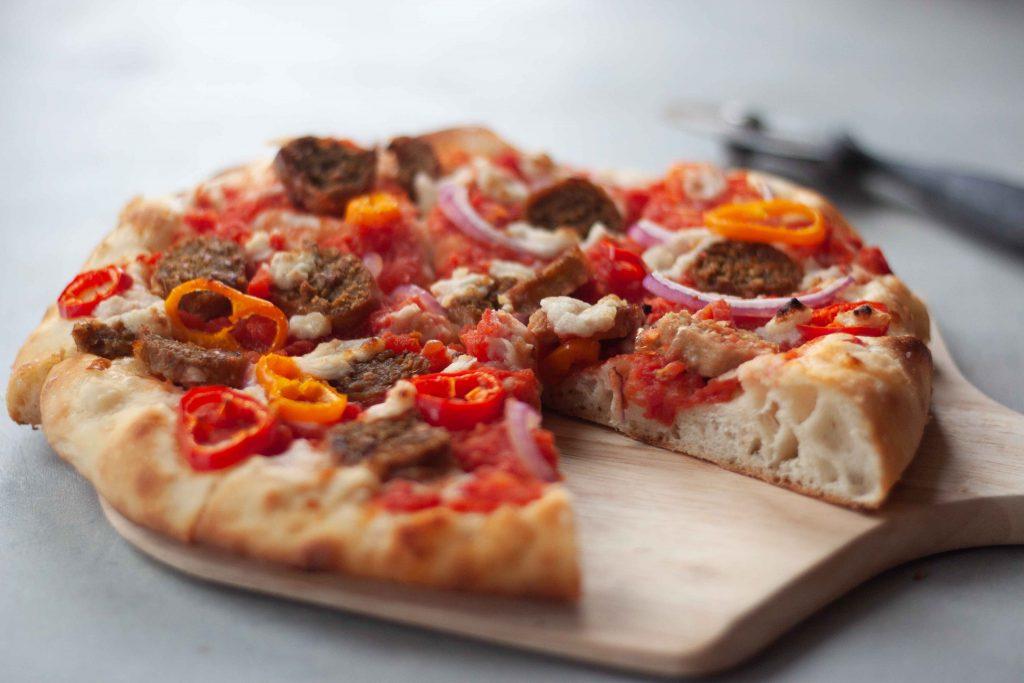sliced sausage pizza on wood board