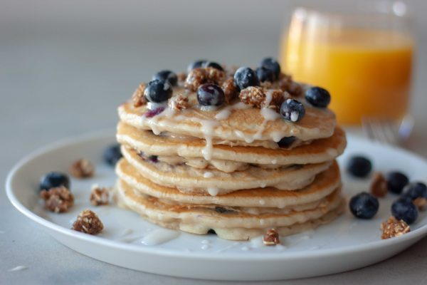 Stack of Blueberry Streusel Pancakes and glass of orange juice.