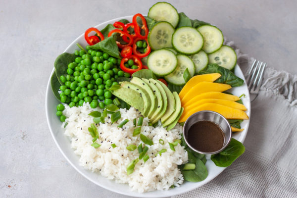 Plate with spinach, rice, sweet peas, red peppers, sliced cucumber, avocado, mango, and a cup of Asian dressing.