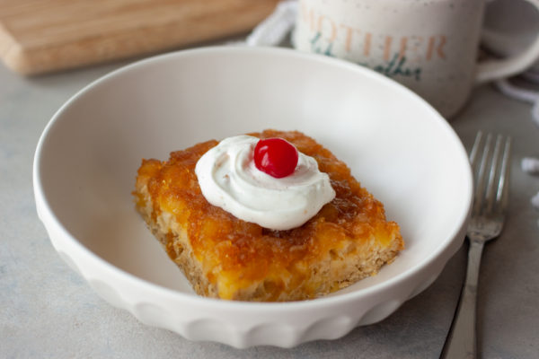 Pineapple Upside-Down Oatmeal Cake in bowl with fork and coffee cup