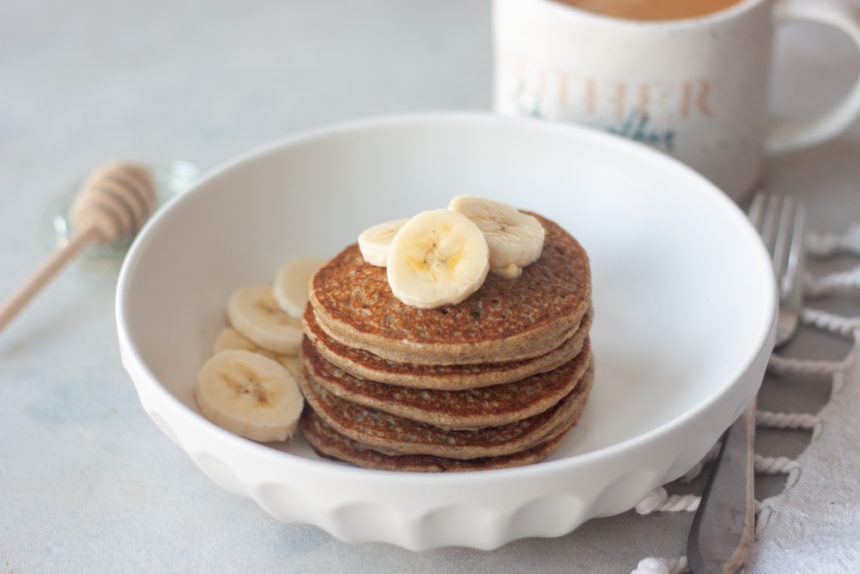 Blender Banana Oatmeal Pancakes in bowl, fork, honey, coffee